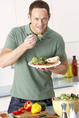 hombre comiendo: Man Eating comidas En Cocina Foto de archivo