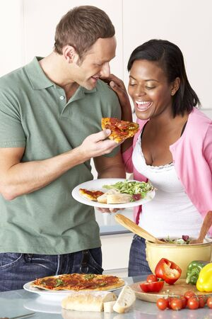 Young Couple Eating Meal In Kitchen photo