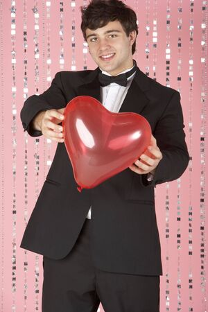 Young Man Dressed In Suit Holding Heart photo