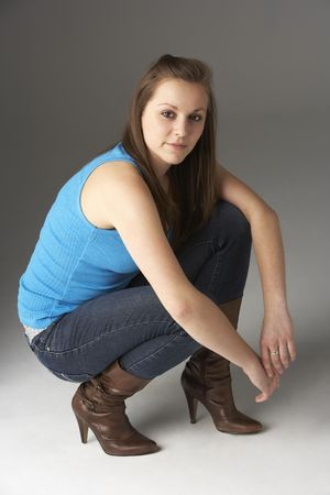 Teenage Girl Kneeling In Studio photo