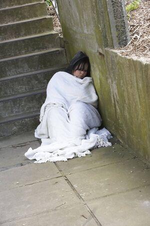 homeless: Chica sin hogar durmiendo en la calle Foto de archivo
