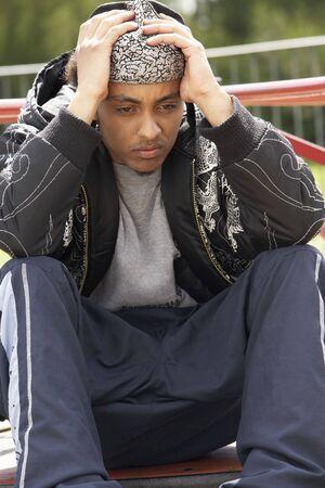 de maras: Joven hombre sentado en Zona de juegos Foto de archivo