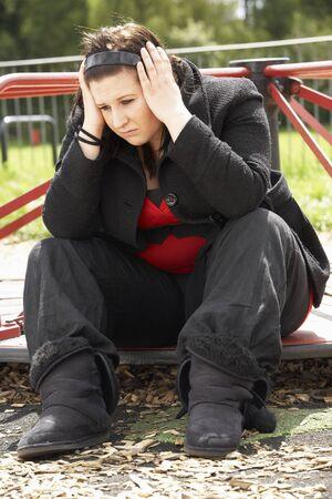 Junge Frau sitzen auf dem Spielplatz Standard-Bild
