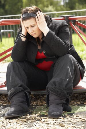 fed up: Young Woman Sitting In Playground