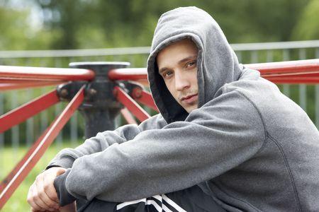 vagabundos: Joven sentado en el patio de juegos Foto de archivo