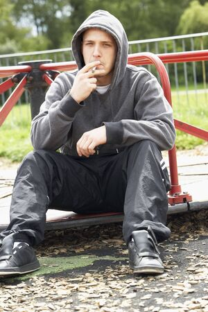 Young Man Sitting In Playground Smoking Joint photo