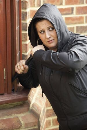 19 year old: Young Woman Breaking Into House Stock Photo
