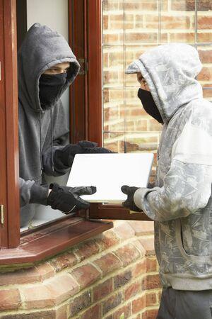 robando: Hombres j�venes rompiendo en casa