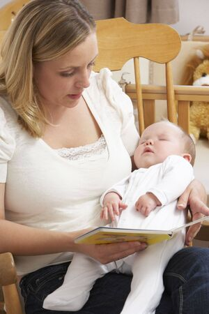 Mother Reading Story To Baby In Nursery photo