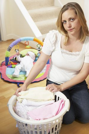 Mother Folding Baby Clothes At Home photo