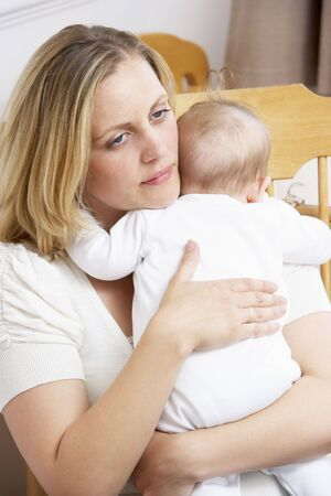 worry: Worried Mother Holding Baby In Nursery