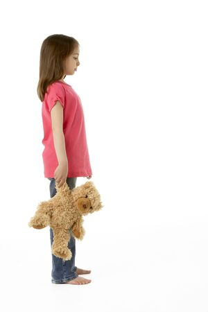 sad lonely girl: Studio Portrait of Girl Standing with Teddy Bear Stock Photo