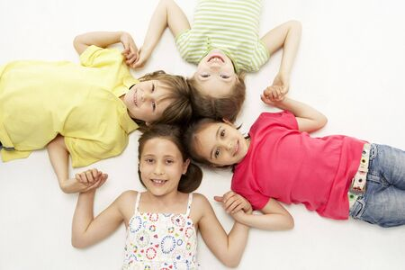 girl lying studio: Circle of four young friends smiling and holding hands Stock Photo