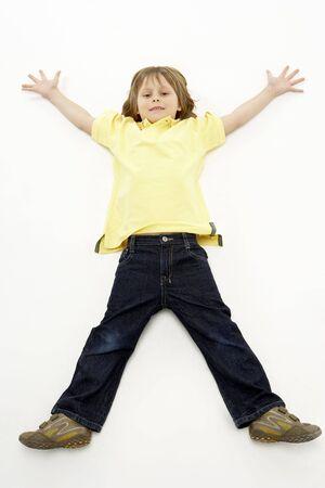 legs spread: Studio portrait of smiling boy sdraiata con le braccia e le gambe divaricate