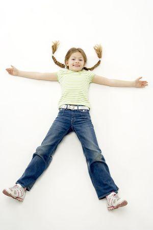 legs spread: Studio portrait di Smiling Girl sdraiata con le braccia e le gambe divaricate