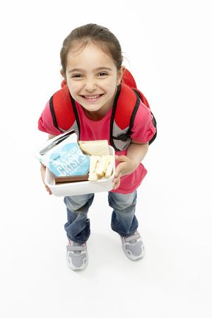 Studio Portrait of Smiling Girl Holding Lunchbox photo