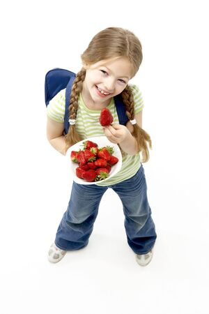 Studio Portrait of Smiling Girl Holding Bowl of Strawberries photo