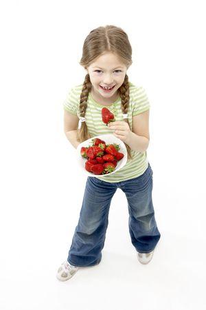 Studio Portrait of Smiling Girl Holding Bowl of Strawberries photo