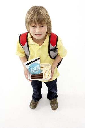 Studio Portrait of Smiling Boy Holding Lunchbox Stock Photo - 5631175