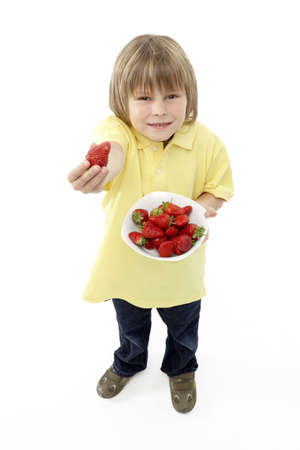 Studio Portrait of Smiling Boy Holding Bowl of Strawberries Stock Photo - 5630961