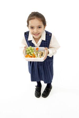 Studio Portrait of Smiling Girl Holding Lunchbox photo