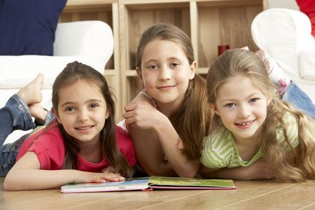 Three Young Girls Reading Book at Home photo