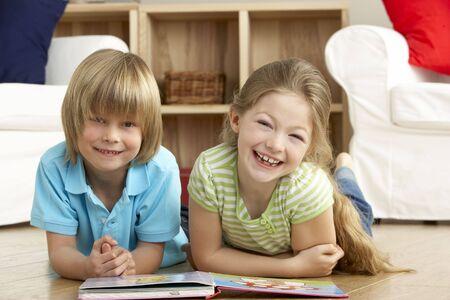 bambini che leggono: Due bambini piccoli di leggere il libro a casa