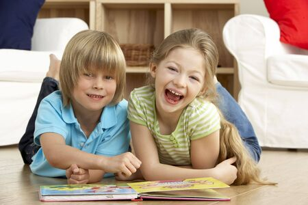 Two Young Children Reading Book at Home photo