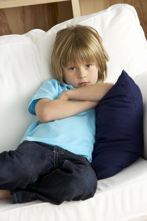 Young Boy Sat on Sofa at Home photo