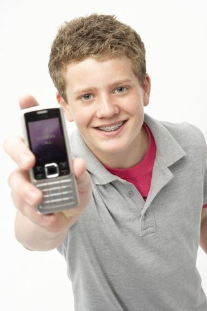 Portrait of Smiling Teenage Boy Holding Mobile Phone photo