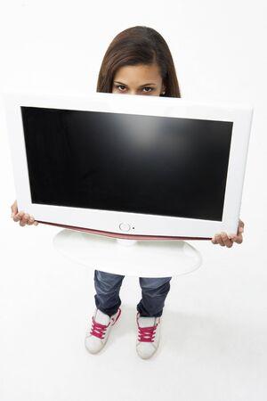 Portrait of Smiling Teenage Girl Holding Television photo