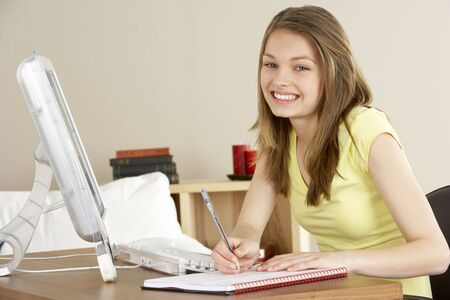 Smiling Teenage Girl Studying at Home photo
