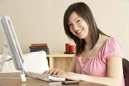 Smiling Teenage Girl on Computer at Home photo