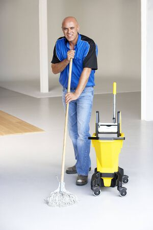 fourties: Cleaner mopping office floor Stock Photo