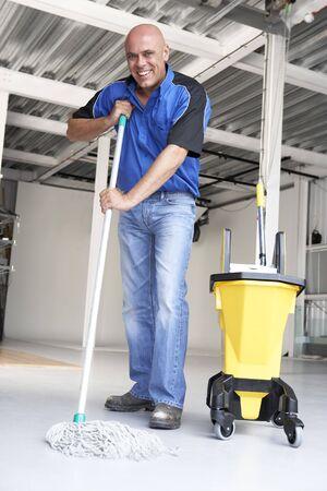 mop floor: Cleaner mopping office floor Stock Photo