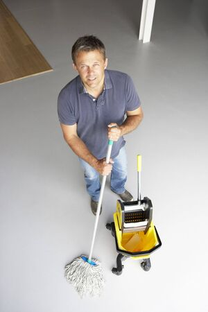 caretaker: Cleaner mopping office floor Stock Photo