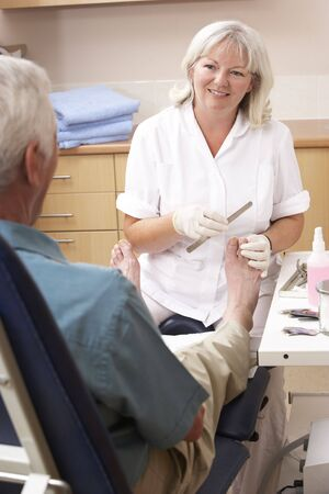 treating: Chirpodist treating client in clinic Stock Photo