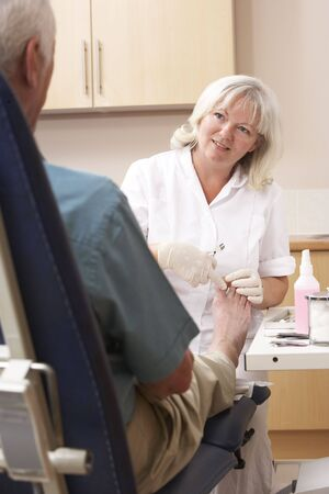 chiropodist: Chirpodist treating client in clinic Stock Photo