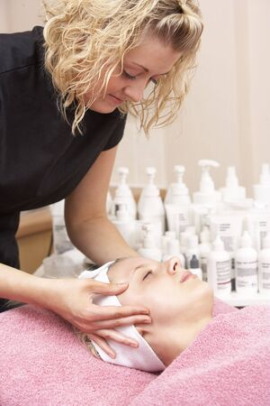 Female masseuse giving client facial photo