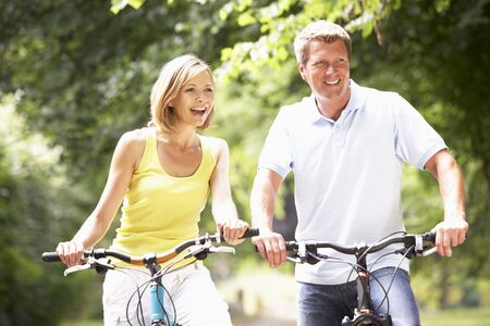 active woman: Couple riding bikes in countryside