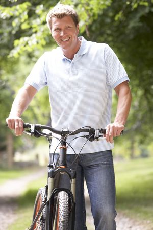 Young man riding bike in countryside Stock Photo - 5631800
