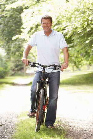 Young man riding bike in countryside Stock Photo - 5632483