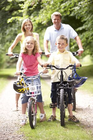 Family riding bikes in countryside photo