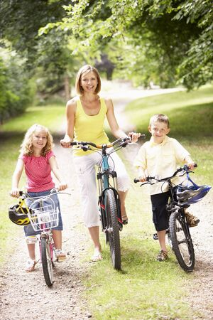 Mother and children riding bikes in countryside photo