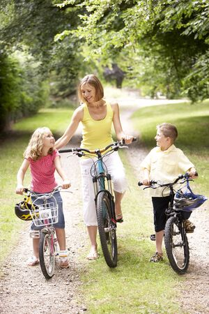 Mother and children riding bikes in countryside Stock Photo - 5632999