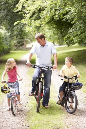Father and children riding bikes in countryside photo
