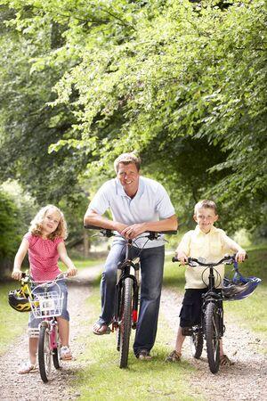 El padre y los ni�os montar en bicicleta en el campo Foto de archivo - 5633085