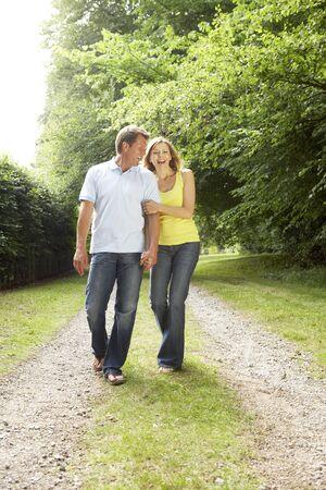 parejas caminando: Pareja de mediana edad caminando en el campo
