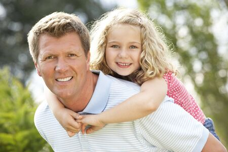 Father giving daughter piggyback Stock Photo - 5632842