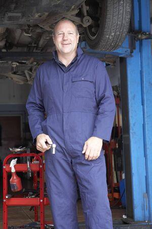 overol: Mec�nico trabajando sobre un auto